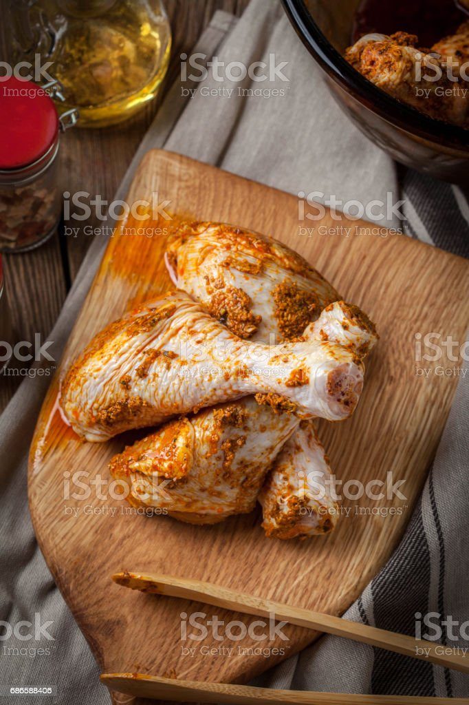 Marinated chicken drumsticks on a wooden chopping board. photo libre de droits
