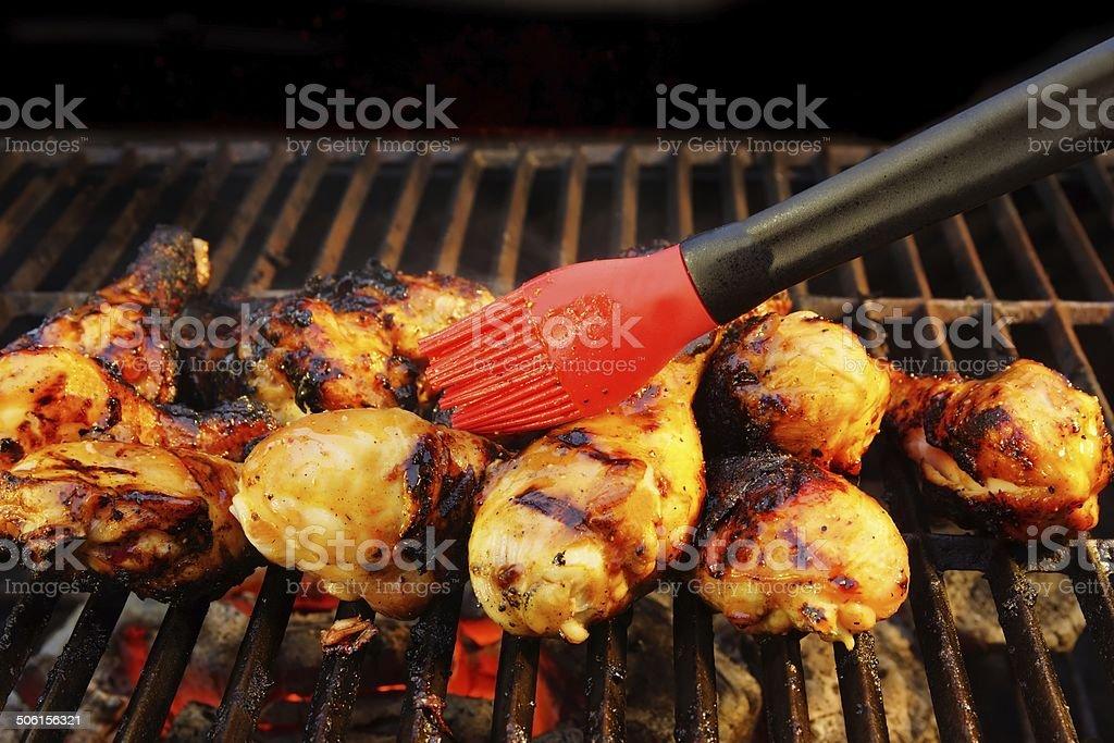 Marinated chicken legs and silicone brush stock photo