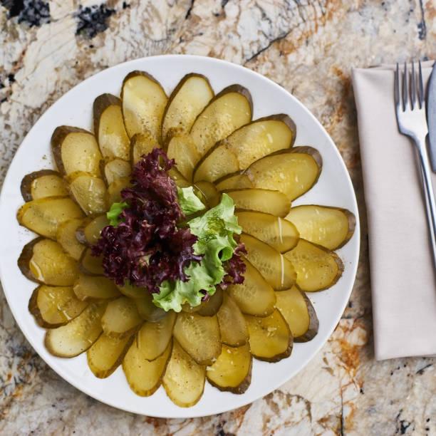 gemarineerde komkommer plakjes op plaat - zout smaakstof stockfoto's en -beelden