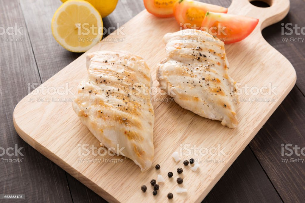 Marinated grilled chicken breasts on the wooden table stock photo