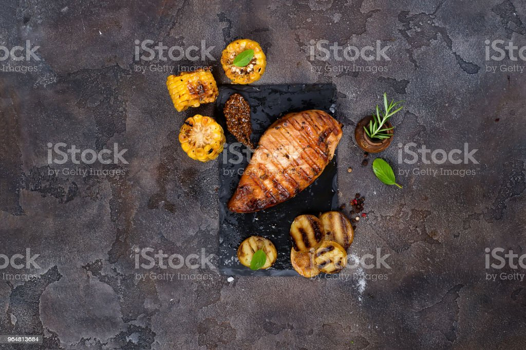 Marinated grilled healthy chicken breasts cooked on a summer BBQ and served with fresh herbs, potatoes and corn royalty-free stock photo