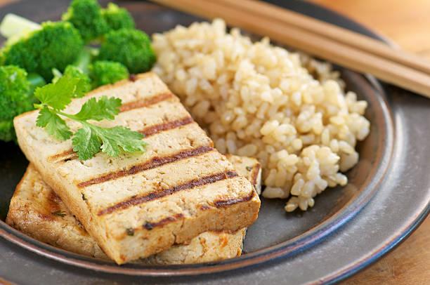 marinierte gegrillter tofu mit braunem reis & brokkoli - mariniertes tofu stock-fotos und bilder