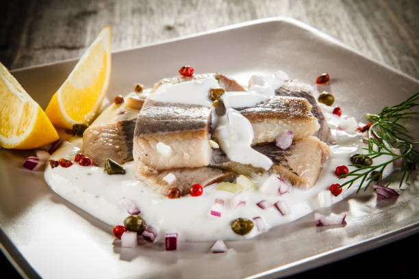 marinated herring fillets in cream - herring stock photos and pictures