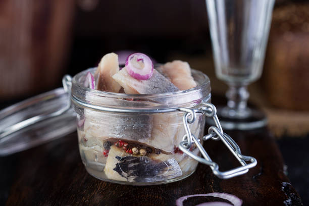 marinated herring in a jar with onion - herring stock photos and pictures