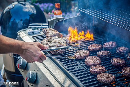 Marinated lamb joint and beef burgers cooking on an outdoor barbecue