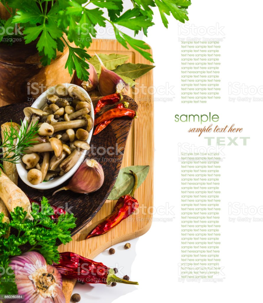 Marinated mushrooms in a cup on the background of spices stock photo