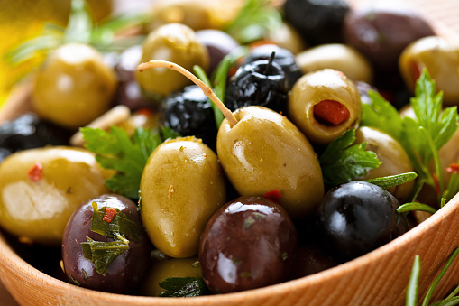 Closeup shot of marinated olives in wooden plate.