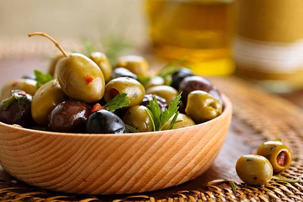 marinated olives with herbs. - grüne olive stock-fotos und bilder