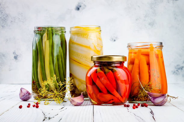 Marinated pickles variety preserving jars. Homemade green beans, squash, carrots, red chili peppers pickles. Fermented food. stock photo