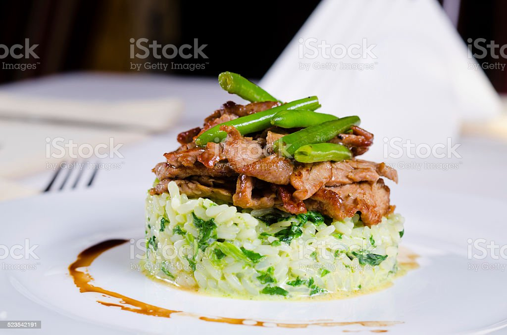 Marinated piquant sliced beef on savory rice stock photo