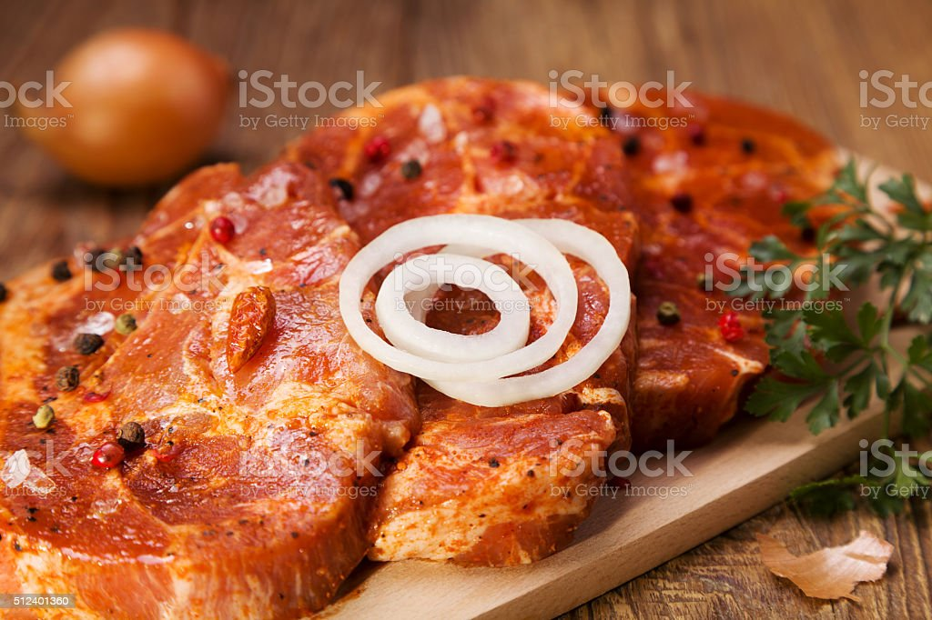 Marinated, raw pork ready for roasting on a wooden table. stock photo