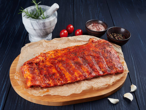 Marinated raw pork spare ribs on crumpled paper on a bamboo cutting board stock photo