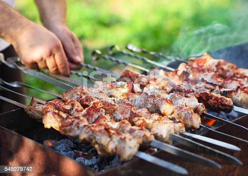 696841580 istock photo Marinated shashlik, lamb meat grilling on metal skewer, close up 545279742