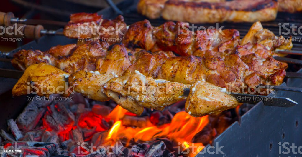 Marinated shashlik preparing on a barbecue grill over charcoal. stock photo