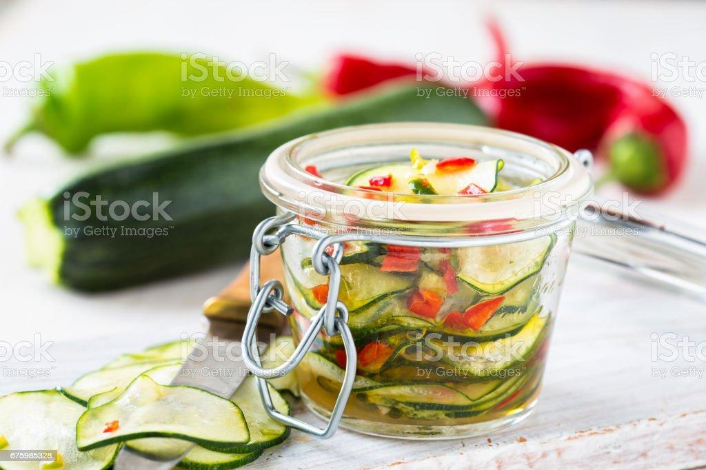Marinated zucchini salad in glass jar stock photo