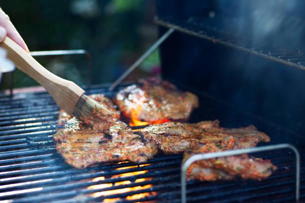marinating 고기 굽고 하는 동안입니다. 그릴에 돼지고기입니다. 정원에서의 바베 큐 - 양념에 재기 뉴스 사진 이미지