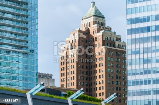 Cityscape of downtown (Coal Harbour) Vancouver,  British Columbia,  Canada.  Iconic art deco Marine Building in the center,  and modern apartments and office buildings to the left and right.  The green, living roof of the Vancouver Trade and Convention Center below.