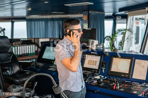 Marine Deck Officer or seaman on navigation bridge of vessel or ship . He is speaking on the mobile cell phone