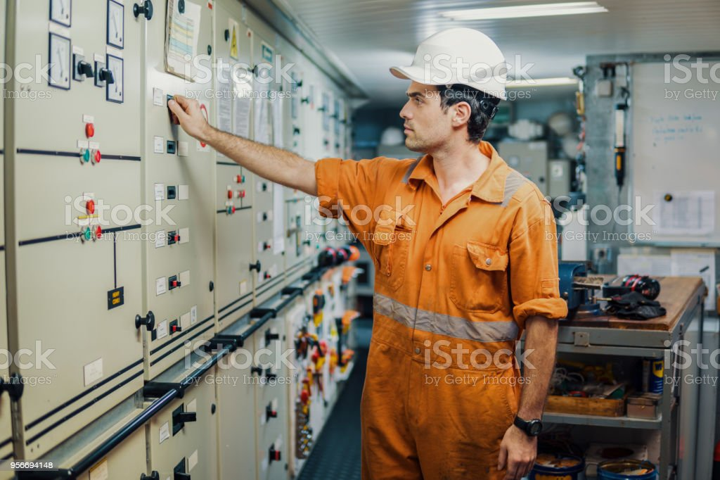 Marine engineer officer starts or stops main engine of ship stock photo