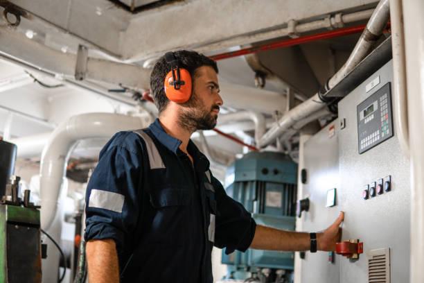Marine engineer officer working in engine room stock photo