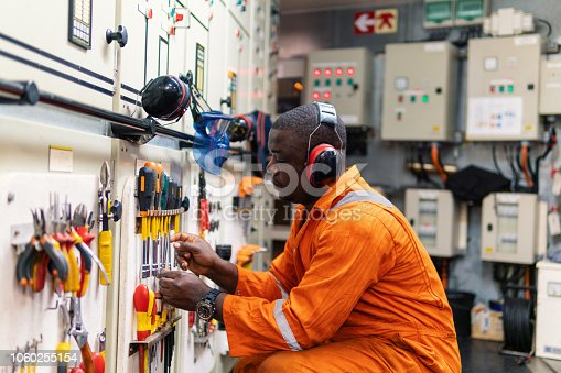 African marine engineer officer in engine control room ECR. He works in workshop and chooses correct tools and equipment