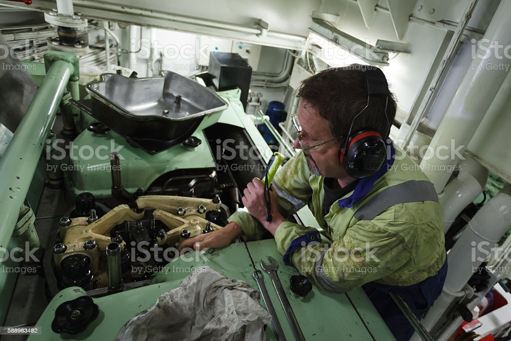 marine engineer working on a ships diesel engine royalty free stock photo