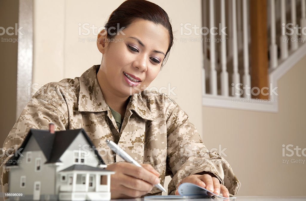 US Marine Female Soldier at Home with Real Estate Paperwork royalty-free stock photo