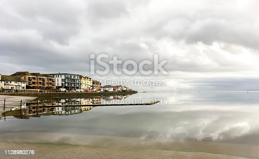 View across marine lake at West Kirby, Wirral, UK.  Houses and apartments can be seen on the far side of the lake and people can be seen on the promenade.