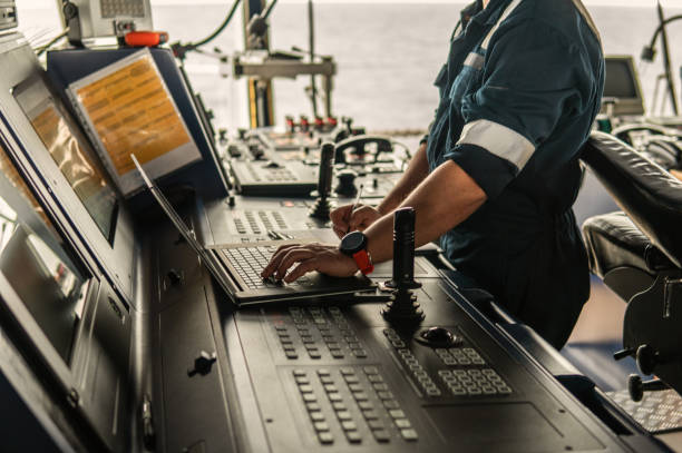 Marine navigational officer is using laptop or notebook at sea stock photo