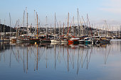 marine parking of sailing boats moored in sea dock reflecting in water