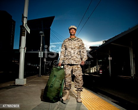 US Marine soldier with a duffle bag at the train station. The model is wearing an official US Marine corps Marpat BDU uniform.