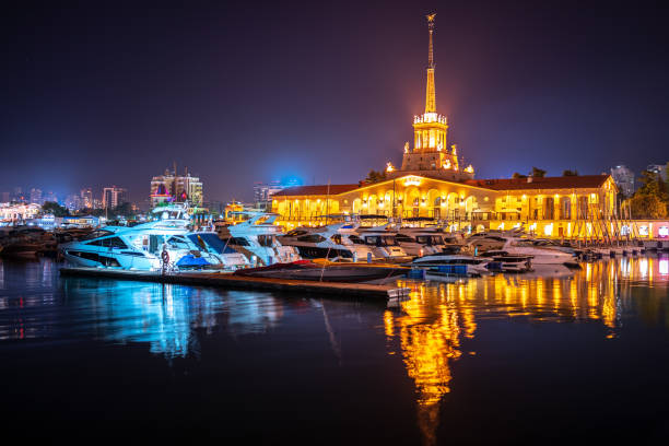 Marine Station of Sochi, illuminated with lights at night with reflection in water Marine Station of Sochi, illuminated with lights at night with reflection in water. Yachts and boats at the pier sochi stock pictures, royalty-free photos & images
