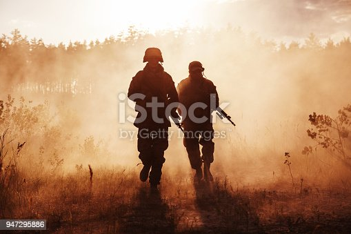 United States Marines in action. Military equipment, army helmet, warpaint, smoked dirty face, tactical gloves. Military action, desert battlefield, smoke grenades