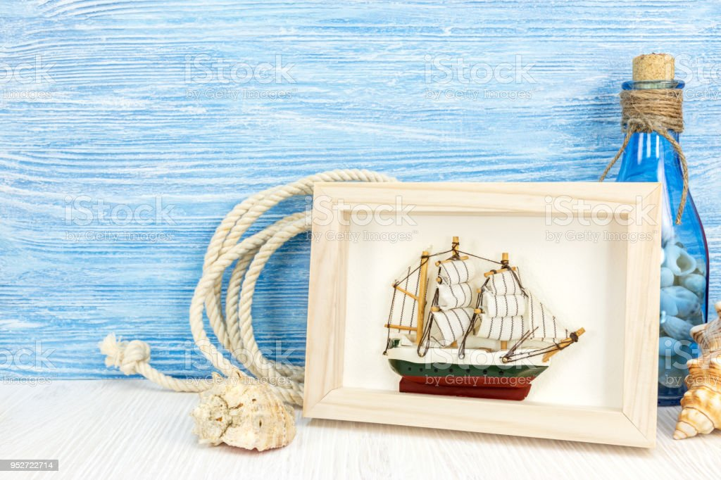 Maritime Background With Picture Frame Ship And Bottle On Blue Wood