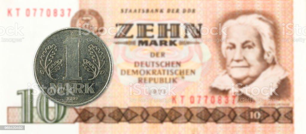 1 mark coin against historic 10 east german mark bank note zbiór zdjęć royalty-free