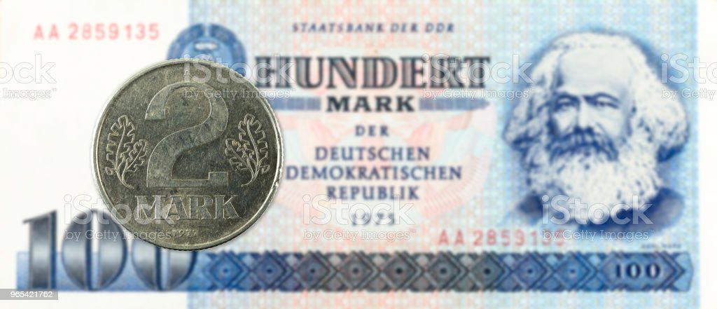 2 mark coin against historic 100 east german mark bank note royalty-free stock photo