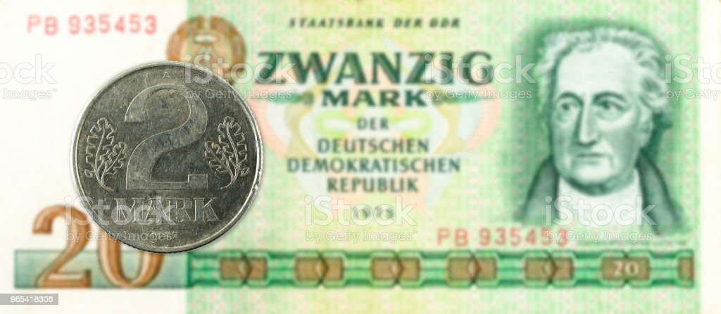 2 mark coin against historic 20 east german mark bank note royalty-free stock photo