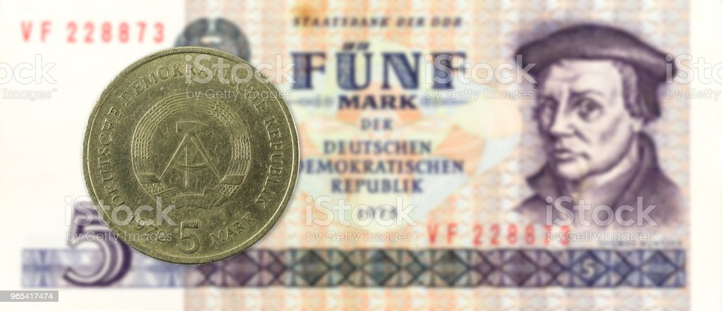 5 mark coin against historic 5 east german mark bank note royalty-free stock photo