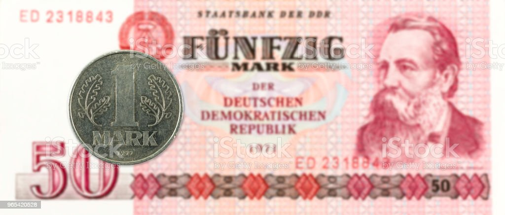 1 mark coin against historic 50 east german mark bank note royalty-free stock photo