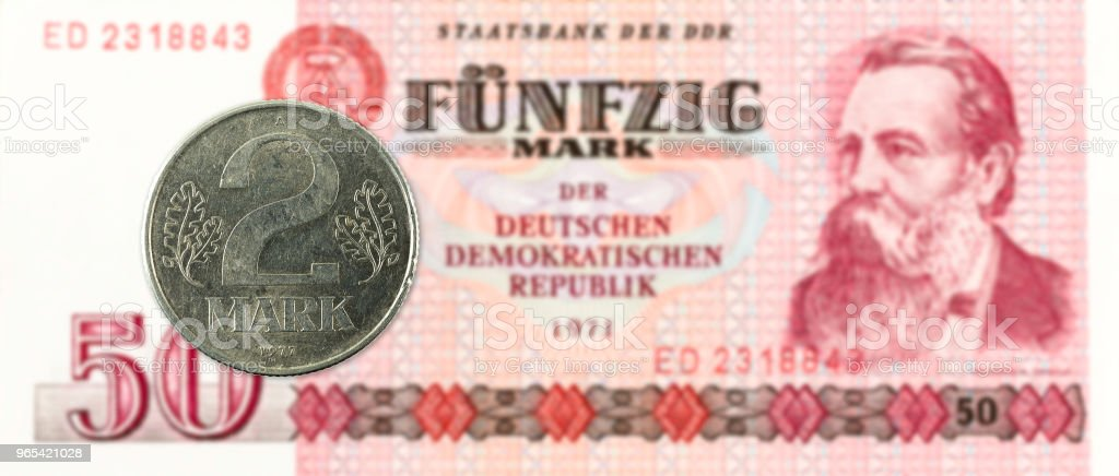 2 mark coin against historic 50 east german mark bank note royalty-free stock photo