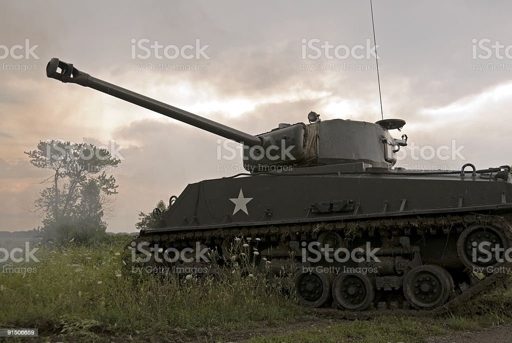 Mark IV Sherman tank driving through field on cloudy day stock photo