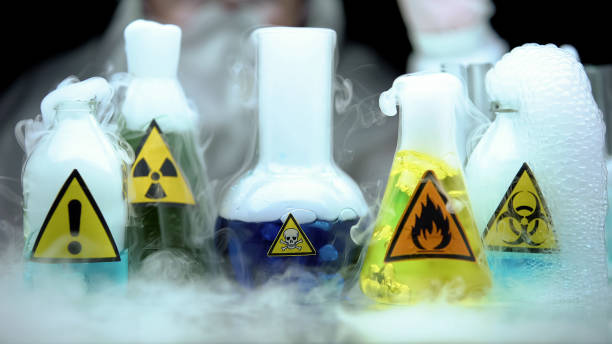 Marked dangerous liquids evaporating in flasks in front laboratory worker Marked dangerous liquids evaporating in flasks in front laboratory worker evaporation stock pictures, royalty-free photos & images