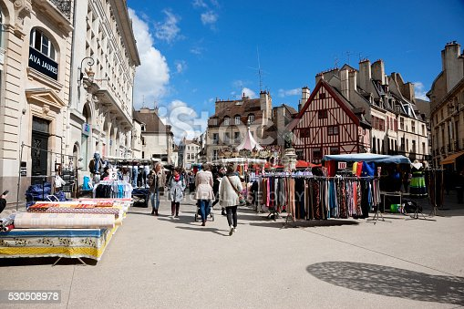 Dijon, France -- April 8, 2016: Market day in Dijon, France. Stalls with merchandise on the the historic city square Place François Rude. People are walking on the square.