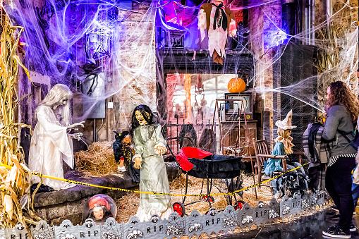 Market food shop interior inside in downtown lower Chelsea neighborhood district Manhattan NYC, people walking by Halloween decorations