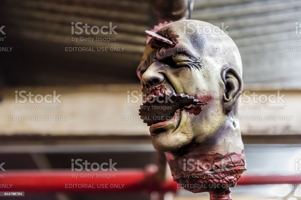 Market food shop interior inside in downtown lower Chelsea neighborhood district Manhattan NYC, closeup of hanging scary spooky severed head Halloween decorations stock photo