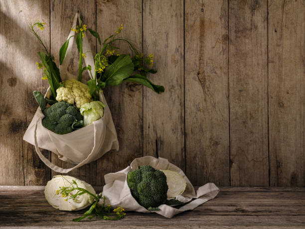 Market fresh green leafy vegetables in a cotton reusable shopping bag hanging from an old hook on an old weathered wooden panel wall, with more vegetables under the bag on a wooden table. - foto stock