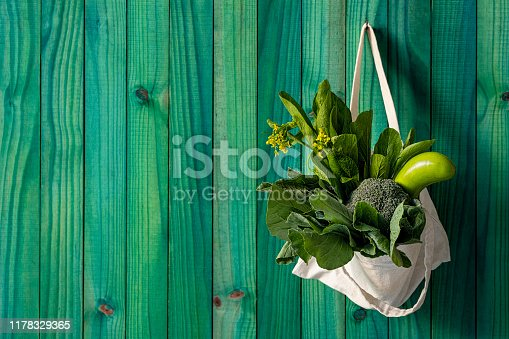 Concept image relating to using reusable natural cotton material shopping bags instead of plastic bags and buying and eating healthy, green, leafy vegetables on a consistent basis instead of eating unhealthy processed foods.