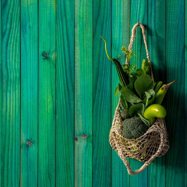 Market fresh, leafy green vegetables in a natural hemp string reusable shopping bag hanging from a hook against a modern turquoise colored wooden panel background wall. stock photo