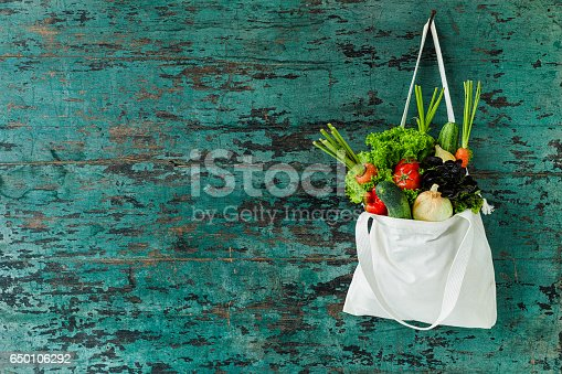 istock Market fresh salad vegetables hanging in a natural cotton recyclable shopping bag by a hook on a wooden turquoise coloured wall. 650106292