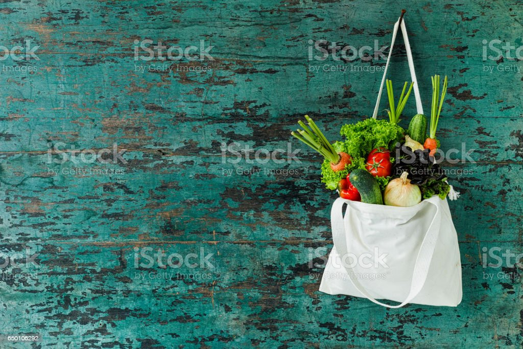 Market fresh salad vegetables hanging in a natural cotton recyclable shopping bag by a hook on a wooden turquoise coloured wall. stock photo